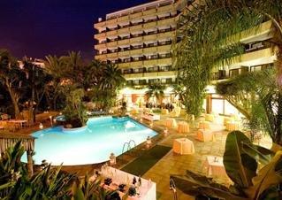 Vista nocturna de la piscina y hotel